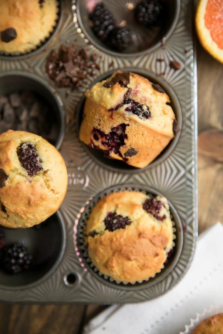 muffin tin with blackberry orange muffins