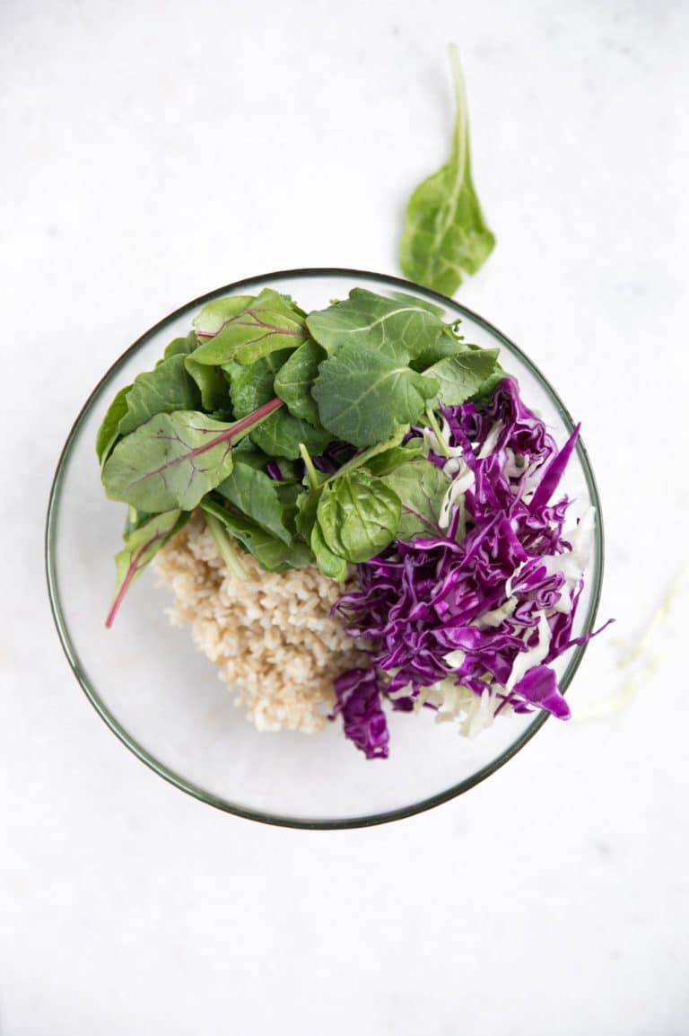 glass bowl with rice, greens, and cabbage