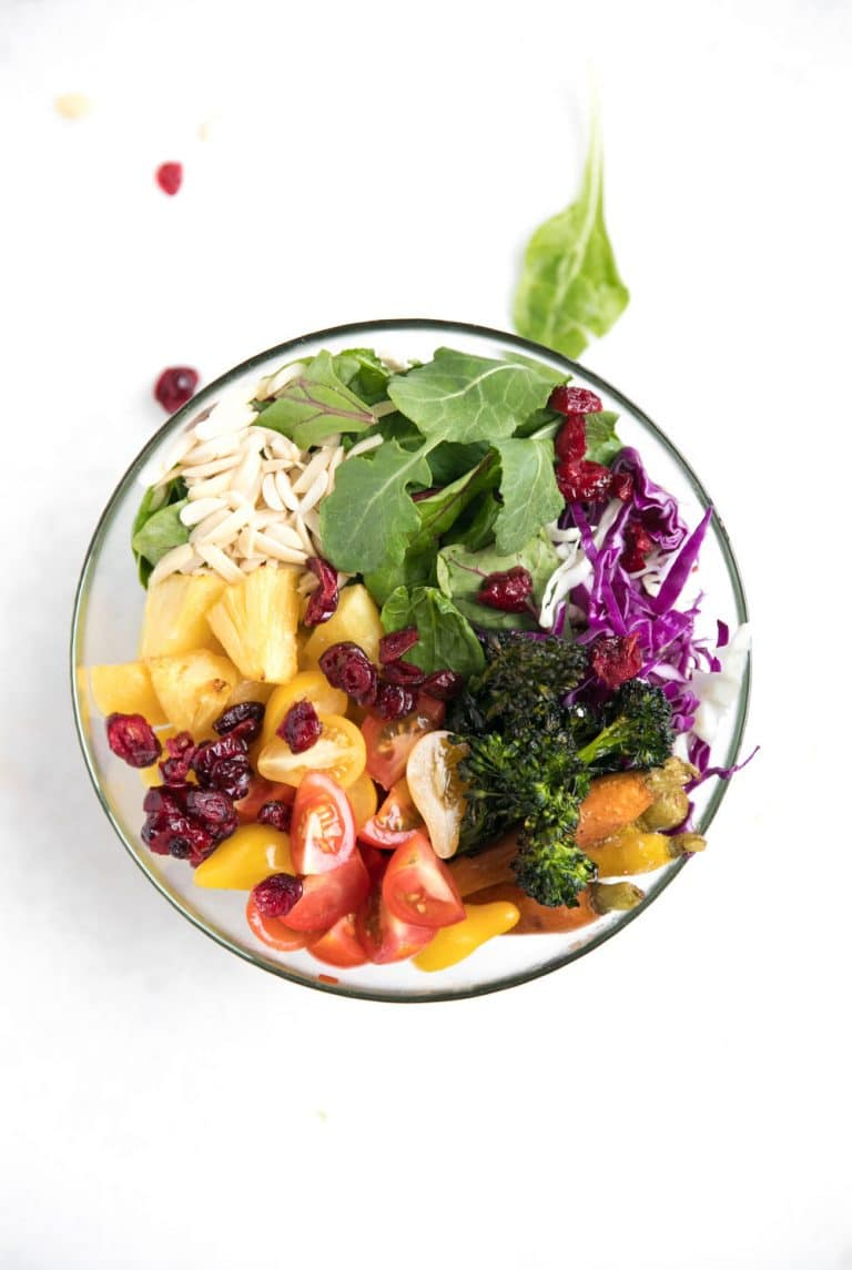 glass bowl with rice, greens, pineapple, tomatoes, carrots, broccoli, cranberries, nuts and cabbage
