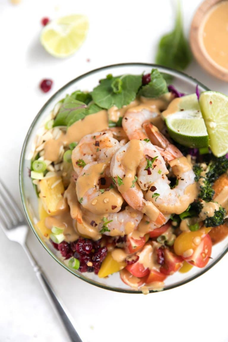 A bowl of food on a plate with shrimp salad buddha bowl