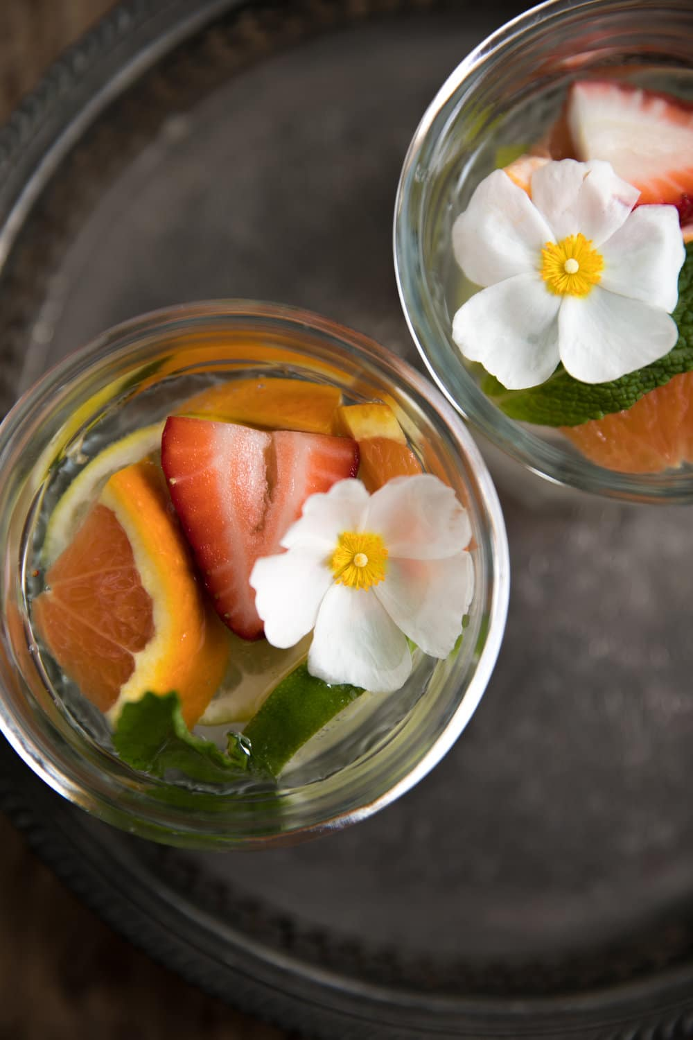 two glasses with sliced fruit and flowers