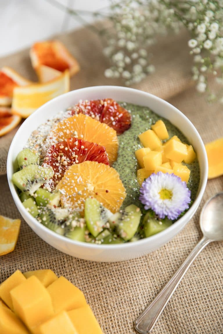 diagonal photo of Matcha Chia Pudding Fruit Bowl sprinkled with coconut and flowers